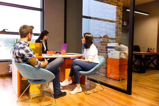 istock Young couple getting advice in office from beautiful business woman 871424182