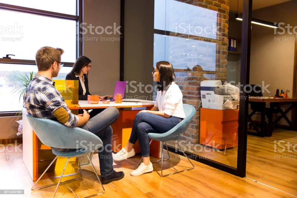 Young couple getting advice in office from beautiful business woman stock photo
