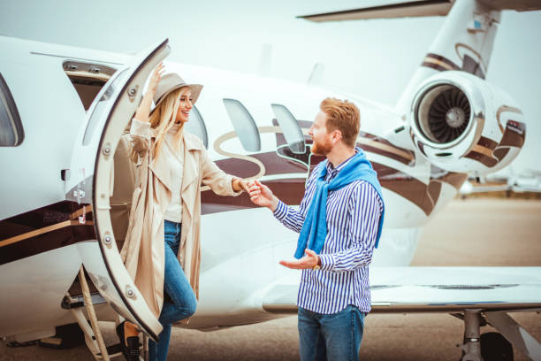 Young couple getting together in front of a private jet Young successful couple meeting together next to a private airplane parked on an airport tarmac. status symbol stock pictures, royalty-free photos & images