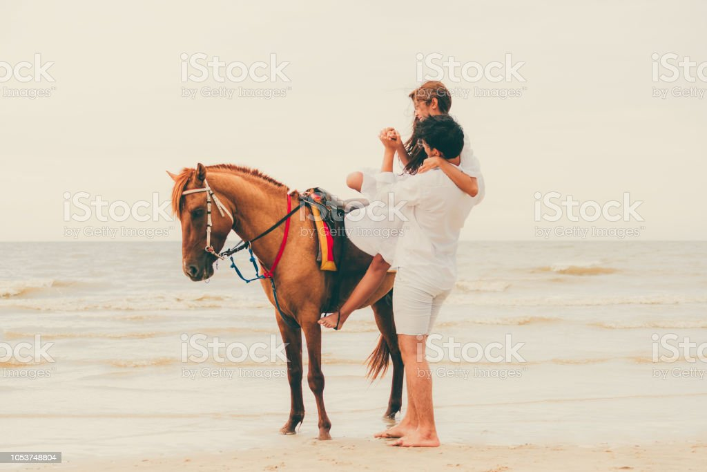 Young couple goes horse riding on tropical beach. stock photo