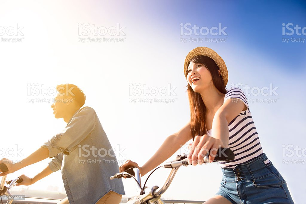 young couple going for  bicycle ride stock photo