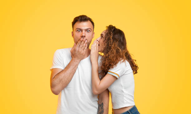 Young couple gossiping on yellow background Pretty young woman telling secret to shocked boyfriend while standing on vibrant yellow background together confidential stock pictures, royalty-free photos & images