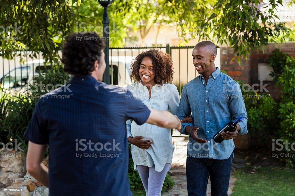 Young couple greeting man during visit at yard - foto de stock