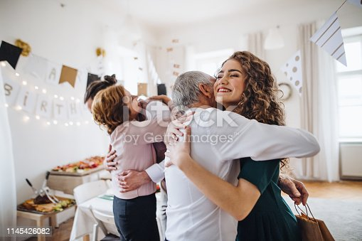 istock A young couple greeting parents or grandparents on indoor birthday party. 1145426082