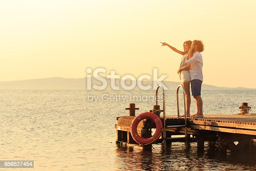 Young people having fun, greeting the sunrise. Both with casual clothes, man with beard and curly hair, woman with long hair.