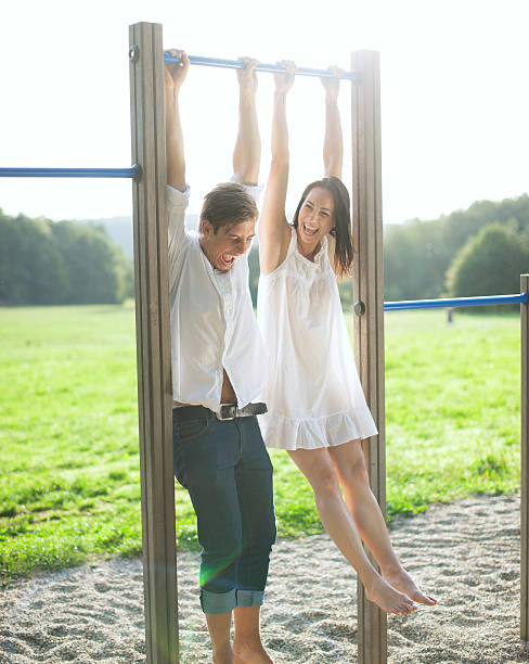 young couple hanging on bars at playground - horizontal bar stock photos and pictures
