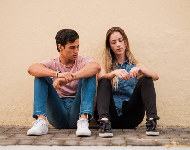 Young couple hanging out together outside stock photo