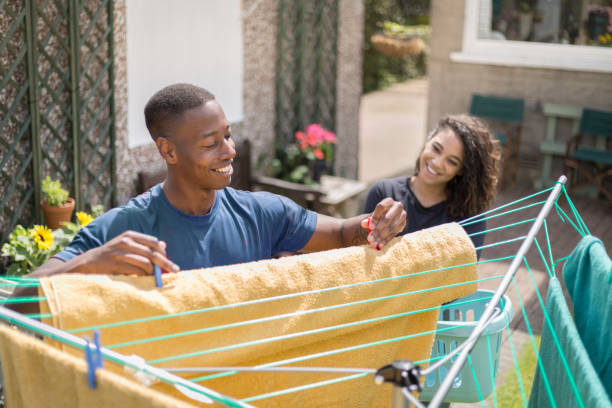 Young couple hanging out washing to dry in garden stock photo