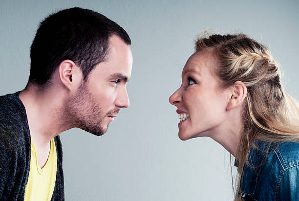 Young couple has a big argument or heated discussion A young man and a young female have a big argument The woman is really mad and looks at the man with clenched teeth The man is staring mean at the woman clenching teeth stock pictures, royalty-free photos & images