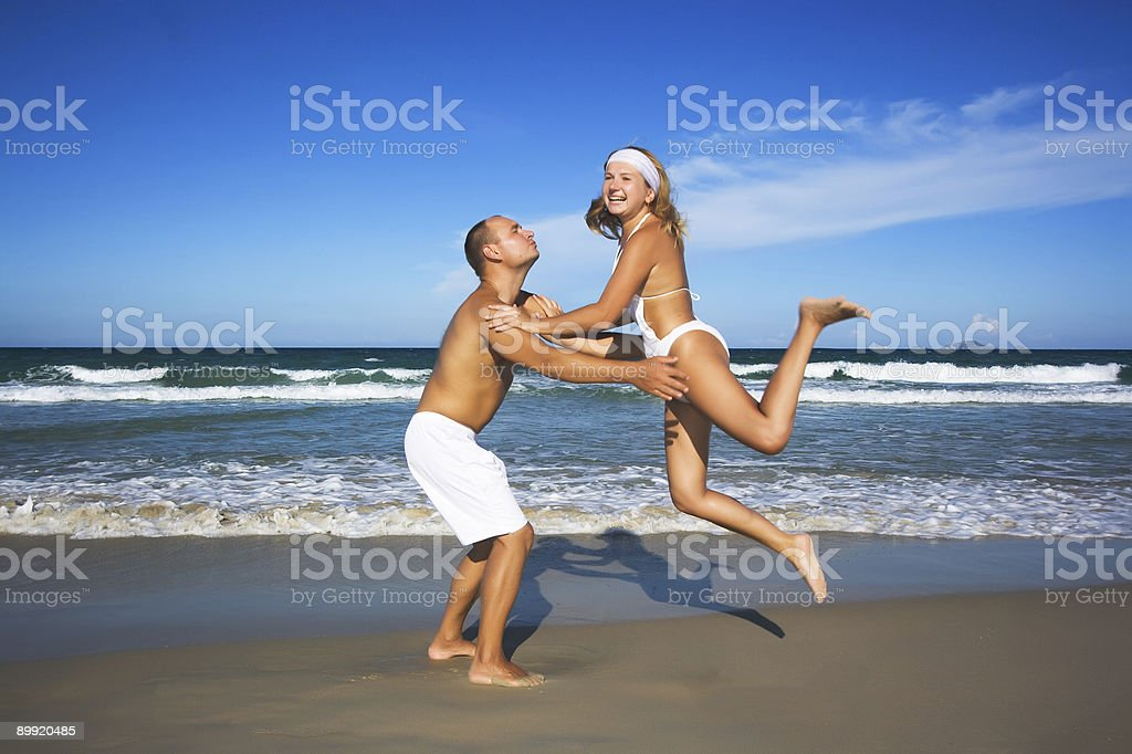Young couple have a fun time on the beach royalty-free stock photo