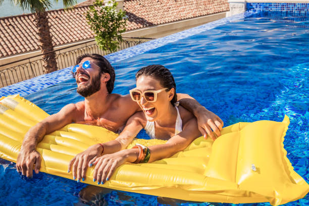 young couple have fun in a pool stock photo