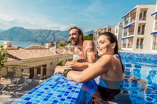 1055009962 istock photo young couple have fun in a pool 1176539900