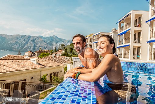 1055009962 istock photo young couple have fun in a pool 1176541524