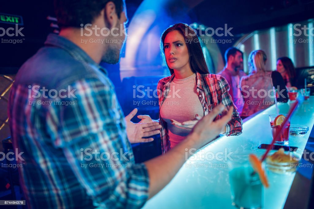 Young couple having a big quarrel in the nightclub stock photo