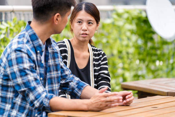Young couple having a conversation outdoors Young couple having a conversation outdoors. Osaka, Japan. September 2017 old mother son asian stock pictures, royalty-free photos & images