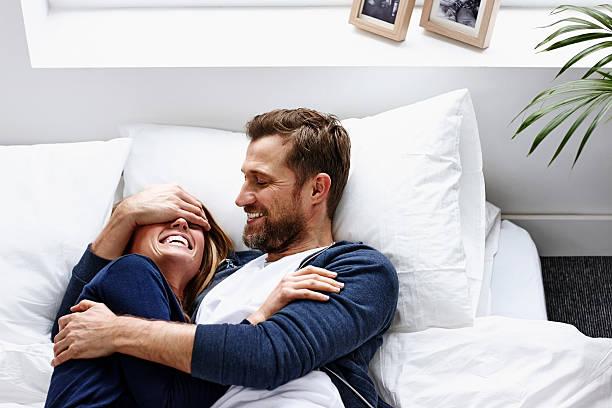 junges paar haben gute zeit im innenbereich - marvel schlafzimmer stock-fotos und bilder