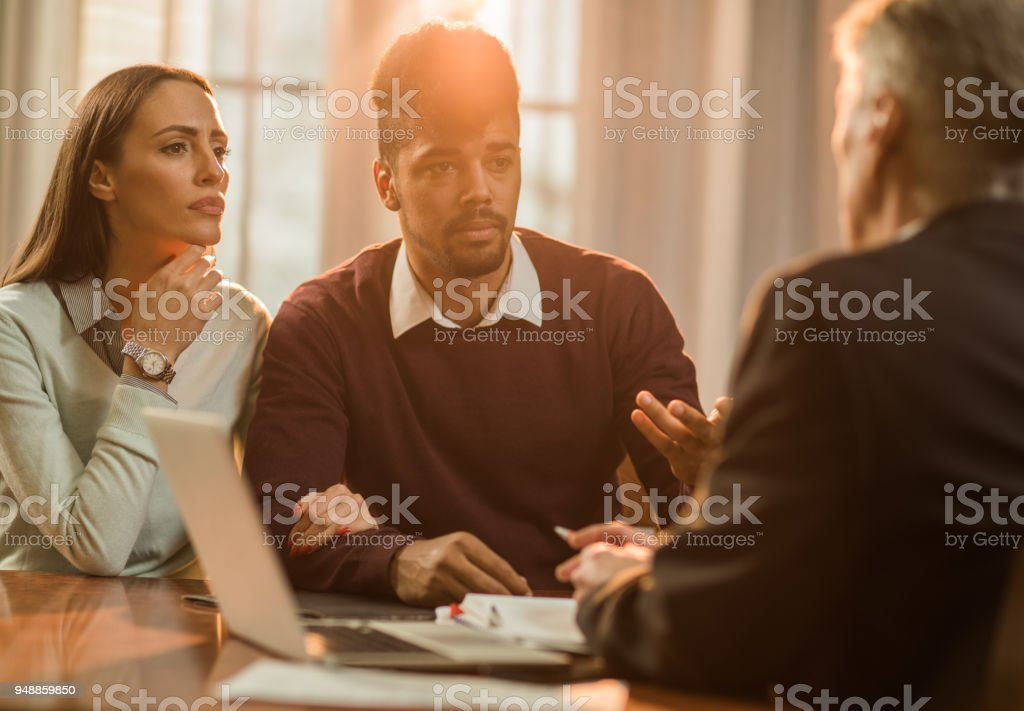 Young couple having a meeting with their insurance agent in the office. stock photo