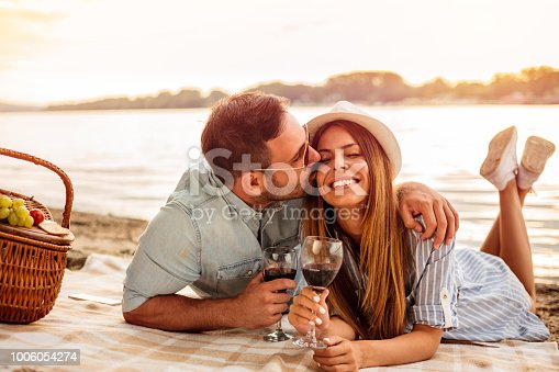 istock Young couple having a picnic at the beach. Man is hugging and kissing his girlfriend 1006054274