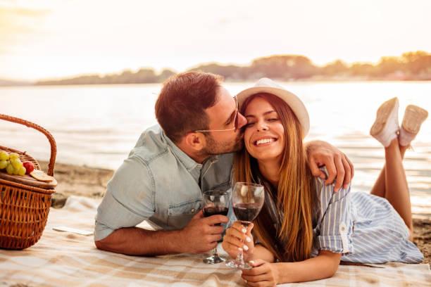 junges paar mit einem picknick am strand. der mensch ist umarmt und küsst seine freundin - romantisches picknick stock-fotos und bilder