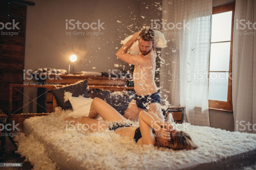 Man and woman, young heterosexual couple in bed, having a pillow...