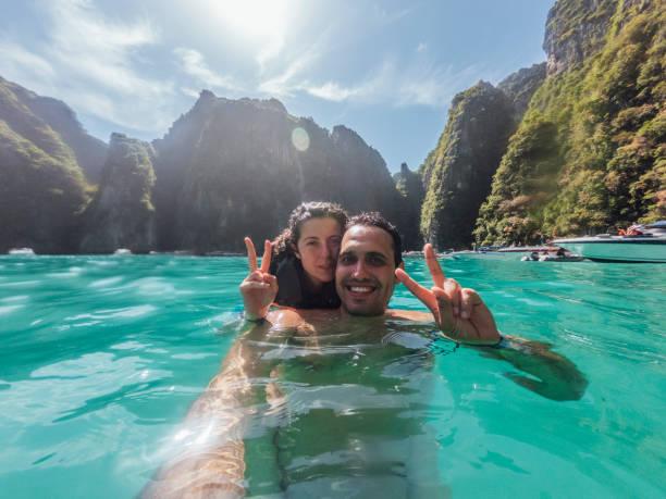 pares novos que têm um selfie no mar da ilha de phi phi-tailândia - beach in thailand - fotografias e filmes do acervo