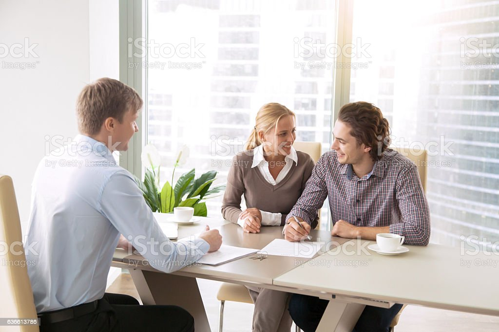 Young couple having a talk with agent stock photo