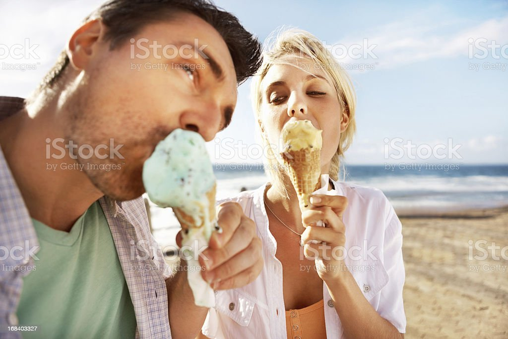 Young couple having an ice cream on the beach royalty-free stock photo