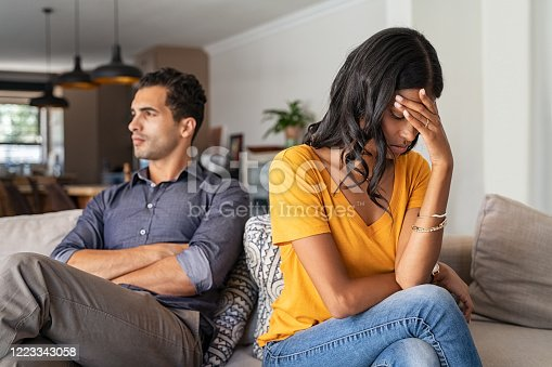 Middle eastern young couple sitting on couch after a fight. Sad indian woman sitting with hand on head after quarrel with boyfriend at home. Angry latin couple ignoring each other on the sofa, having relationship troubles.