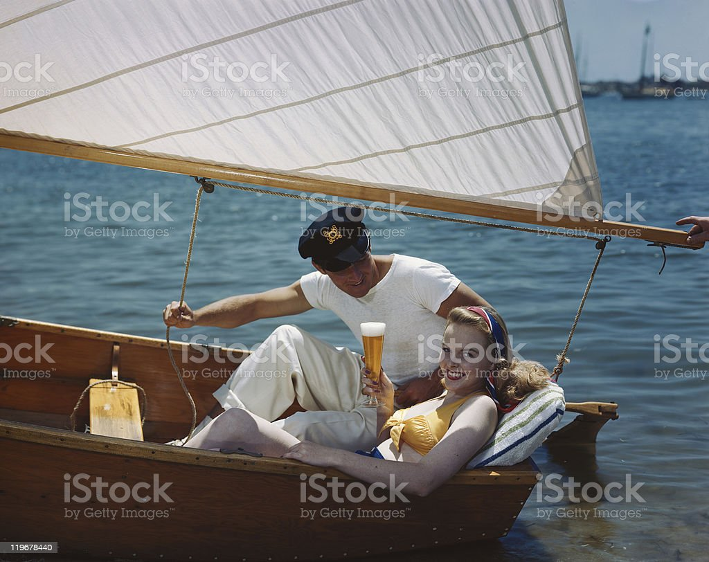 Young couple having beer in sailing boat stock photo