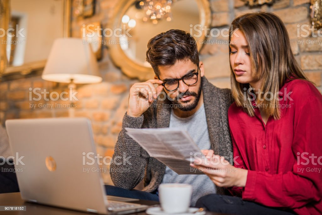 Young couple having bills to pay. stock photo