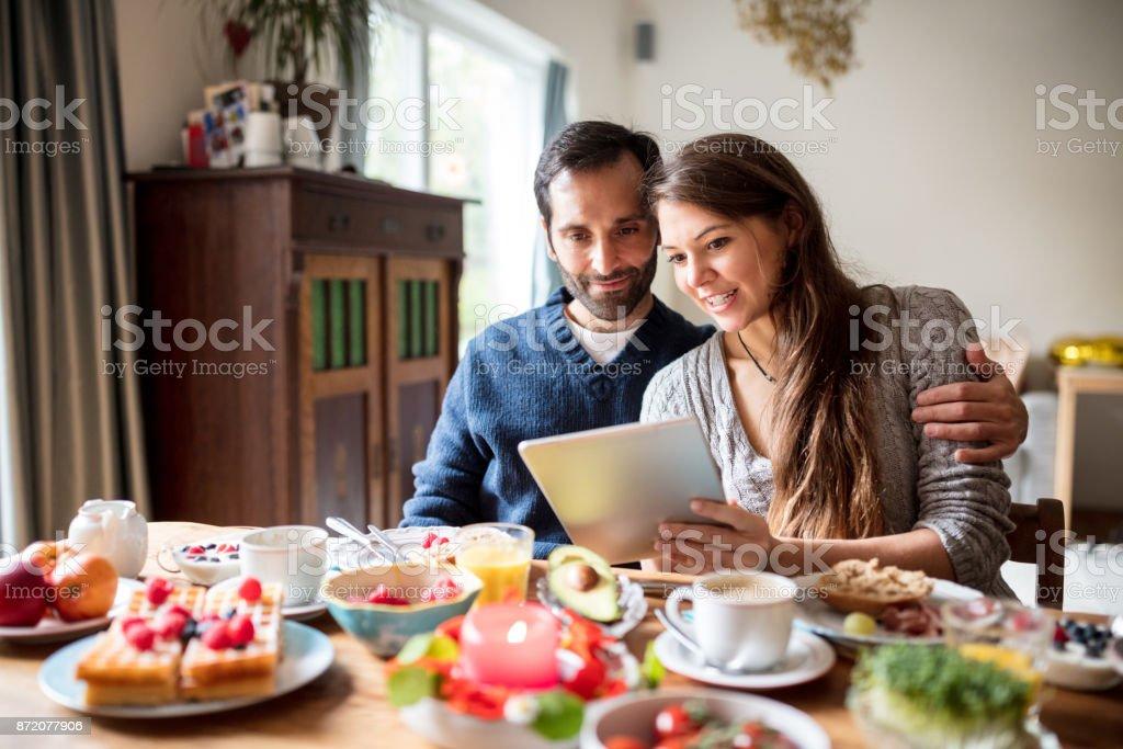junges Paar frühstücken und mit Blick auf digital-Tablette – Foto