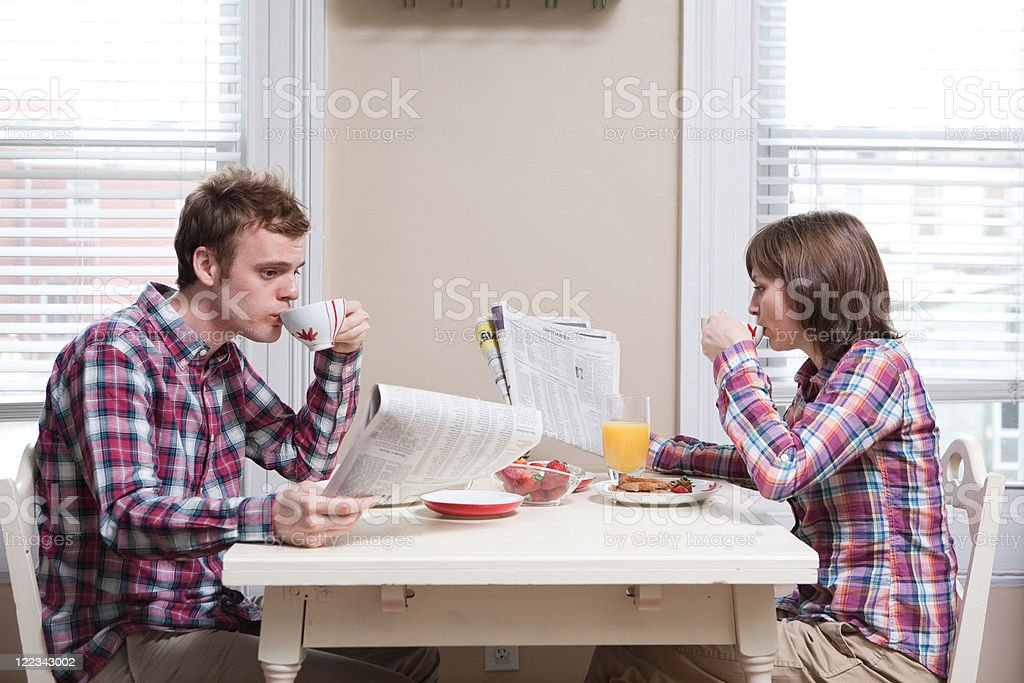 Young couple having breakfast at kitchen table stock photo