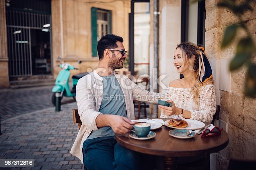 Young happy couple eating breakfast and drinking coffee at stone built coffee shop in Italian streets