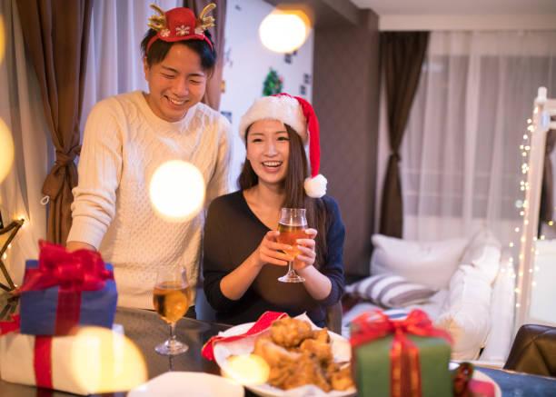 junges paar mit weihnachts-party zu hause - weihnachten japan stock-fotos und bilder