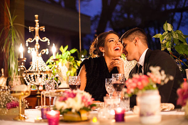 Young couple having dinner at a restaurant. Young couple having romantic dinner at the restaurant. Woman is laughing while man whispering something at her ear. table for two stock pictures, royalty-free photos & images