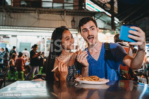 Young couple having dinner together at the night market and taking a selfie