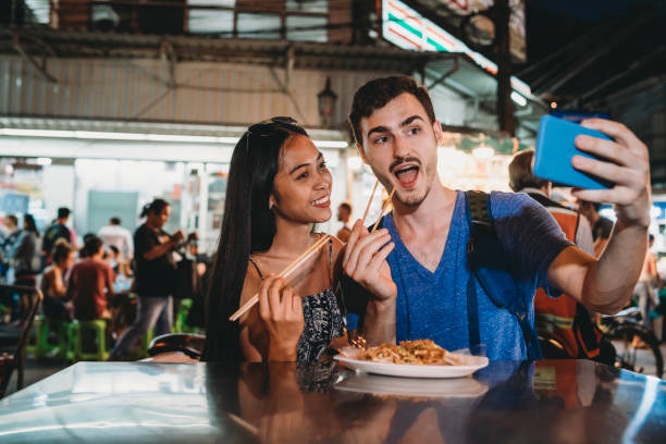young couple having dinner together at the night market and taking a selfie - foodie stock photos and pictures