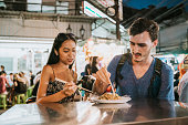 Young couple having dinner together at the night market