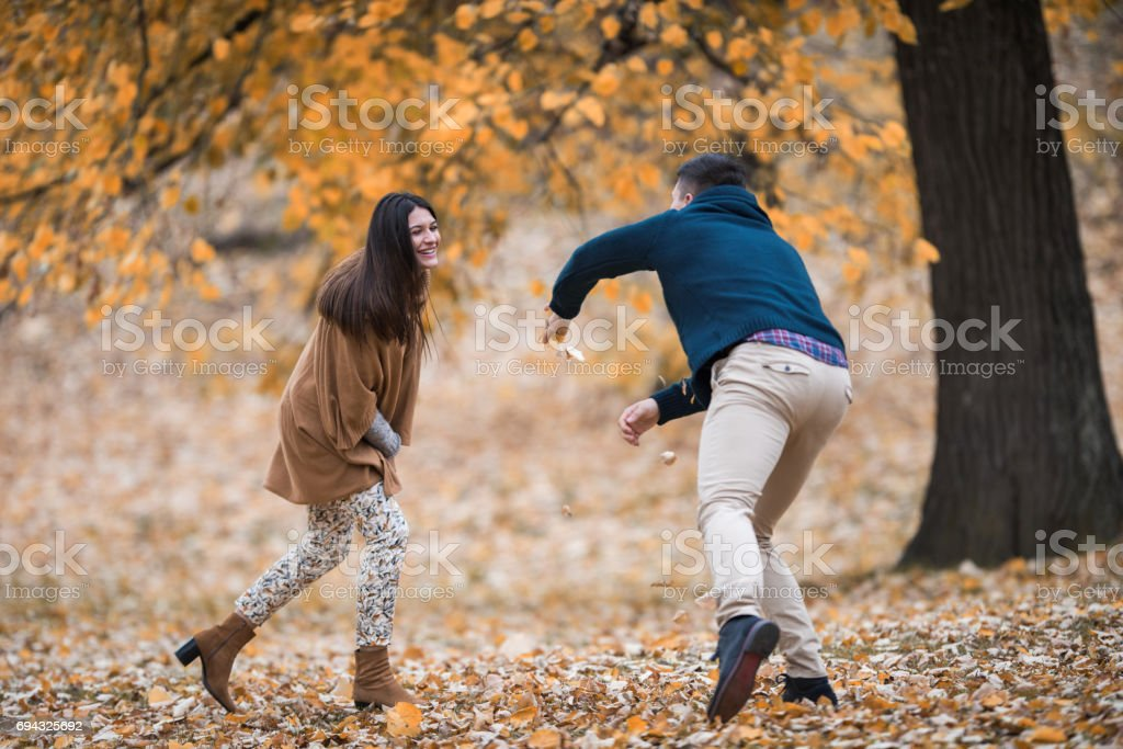 Young couple having fun and playing with autumn leaves in nature. stock photo