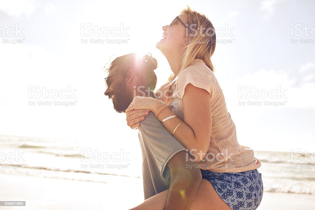 Young couple having fun at the beach stock photo