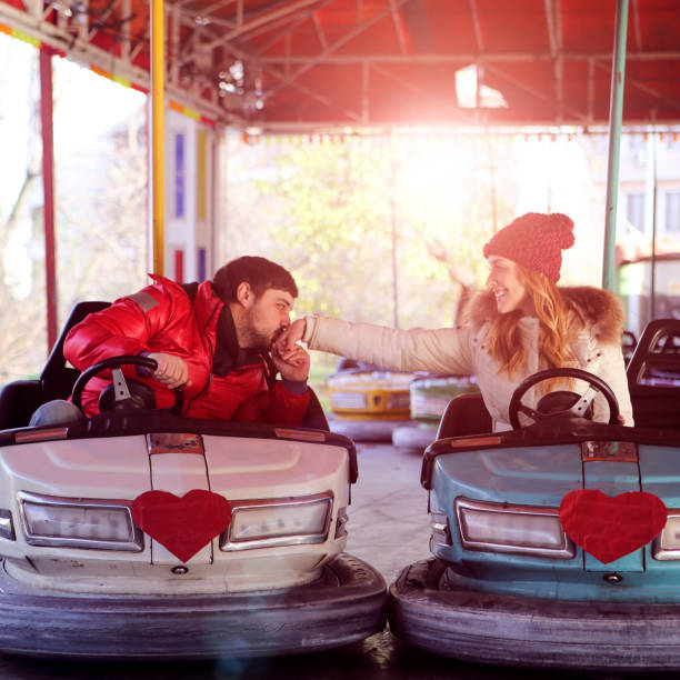 Young Couple Having Fun Driving Bumper Cars. Young Cheerful Couple Having Fun Driving Bumper Cars with heart shapes in front. Young man kissing hand of her beautiful young woman. Engagement kiss. kissinghand stock pictures, royalty-free photos & images