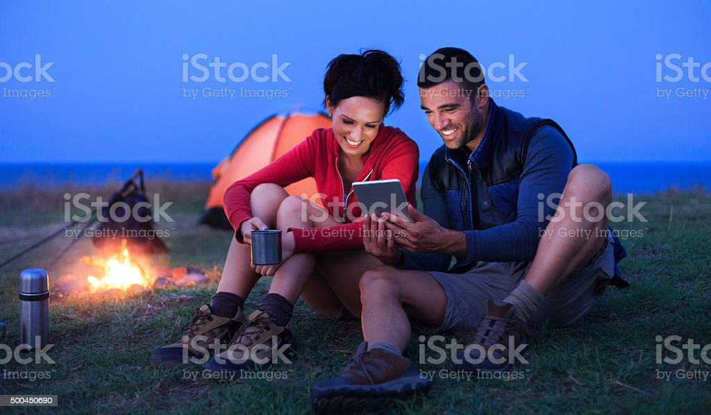 Young couple having fun in front of their tent stock photo