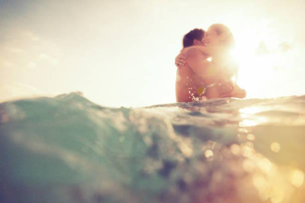 若いカップルは、海でお楽しみください。 - 水につかる ストックフォトと画像