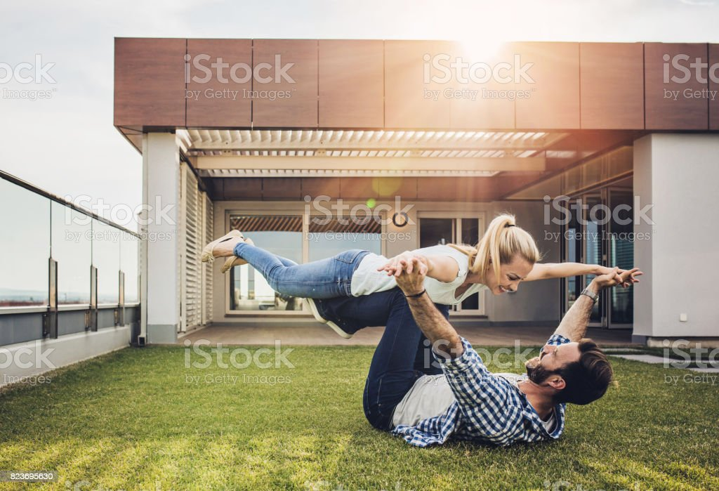 Young couple having fun on a terrace in front of a penthouse. stock photo