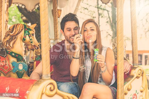 Young adult couple on a carousel are playing and having fun with soap bubbles