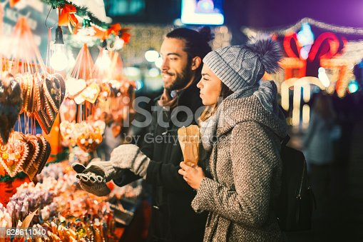 Couple having fun outdoors at winter. They are standing and choosing sweets, buying candies.