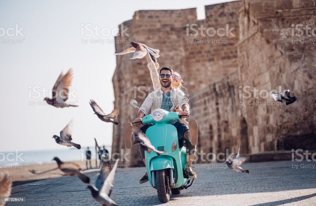 Young couple having fun riding scooter in old European town stock photo