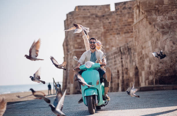 young couple having fun riding scooter in old european town - travel imagens e fotografias de stock