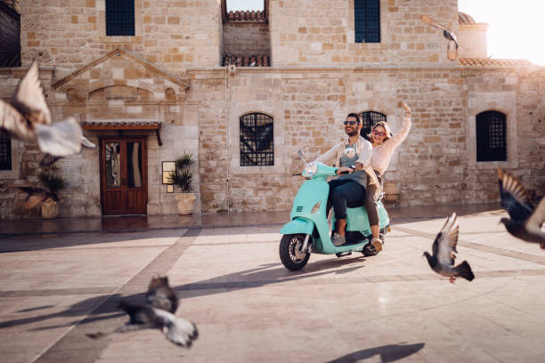 Young couple having fun riding vintage scooter in European town Tourists couple on summer holidays in Italy having fun riding retro scooter in stonebuilt village wundervisuals stock pictures, royalty-free photos & images