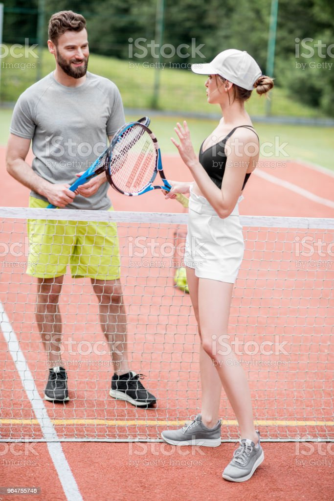 Young couple having fun standing on the tennis court royalty-free stock photo